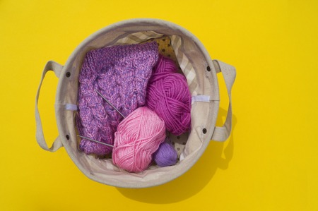 Lilac, pink and purple tangles of threads lie in a basket on a yellow background. Favorite hobby is creative. Lesson for women. Archivio Fotografico