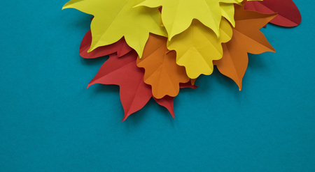 Leaves of paper fall red, orange, yellow leaf fall. Blue background. Handmade origami.