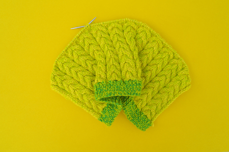 Yellow and green coats of wool lie on the table. Favorite hobby is knitting. Home cosiness. Stock fotó