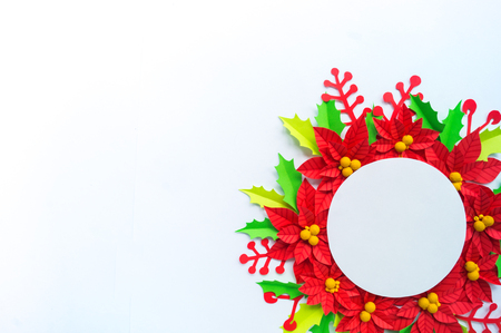 Paper flower poinsettia and leaves of holly. Christmas wreath. White background. Colors are green, red, yellow.
