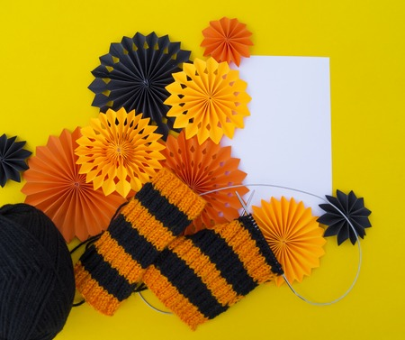 The process of knitting gaiters on a Halloween holiday. Witch costume. Autumn cosiness. Yellow background. Archivio Fotografico