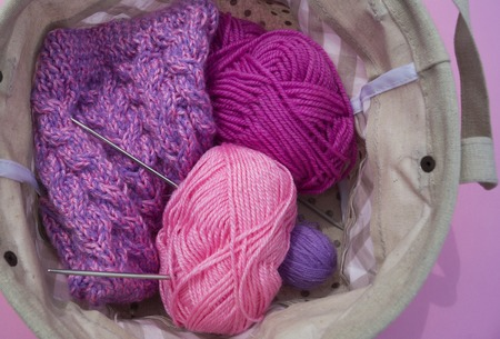 Lilac, pink and purple tangles of threads lie in a basket on a pink background. Favorite hobby is creative. Lesson for women.