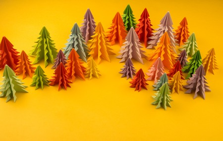 Multicolored paper Christmas tree on a yellow background. Christmas holiday. Children's holiday.