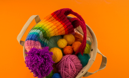 Rainbow cap made of wool on an orange background. Copy space. View from above. Striped knitted warm hat with pompon.