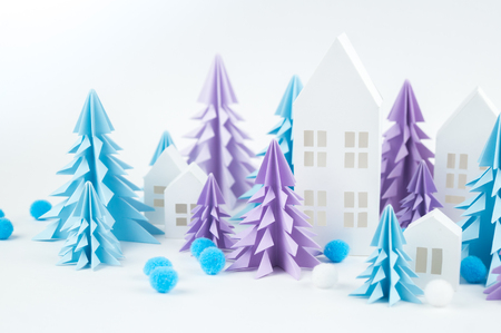Christmas tree of blue and lilac paper on a white background. Snow white and blue. House of paper craft.