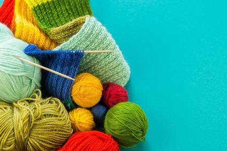 Robić na drutach tęczowy szalik i czapkę. Kosz z kulkami z wełny, druty do robienia na drutach. Niebieskie tło. Ulubiona praca to hobby.