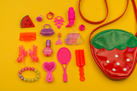 Toys for girls from a bag in the form of strawberries. children's cosmetics and jewelry Flat lay Pink toys on a yellow background. View from above. Kindergarten.