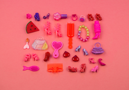 Toys for girls from a bag in the form of strawberries. children's cosmetics and jewelry Flat lay toys on pink background. View from above. Kindergarten.
