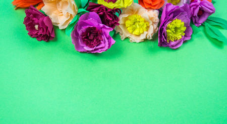 Utensils and tools for making crepe paper flowers on green background. Cosmos flower bouquet Stock Photo