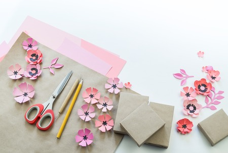 Packing a festive box with ribbons and flowers. Flower made of paper. Favorite hobby. View from above.