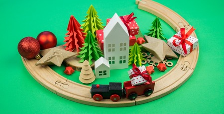 A toy wooden train carries a box with a gift to the child. Christmas magic city. Paper tree and star, decoration for the holiday. New Years toy.