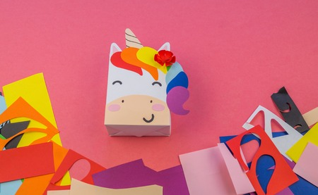 Unicorn of paper on a pink background. Master class hand-made. A magical animal. Materials for creativity and tools.