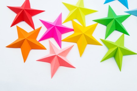 A star made of rainbow-colored paper. Festive decor starry sky. White background. Favorite hobby. Creativity with children. Фото со стока