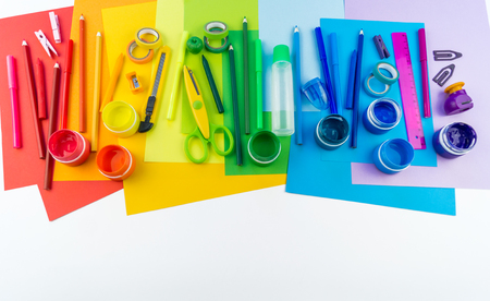 School accessories are laid out in the form of a rainbow. white background. Happy back to school student. Art and crafts for kids. Child learning rainbow colors, alphabet letters and numbers.