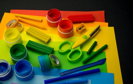 School accessories are laid out in the form of a rainbow. Black background.Happy back to school student. Art and crafts for kids. Child learning rainbow colors, alphabet letters and numbers. 免版税图像