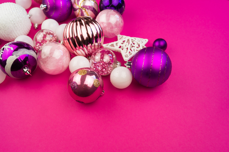 Gentle pink and purple baubles on a pink background. Christmas mood. Festive decor. Sequins and glitter for a party.