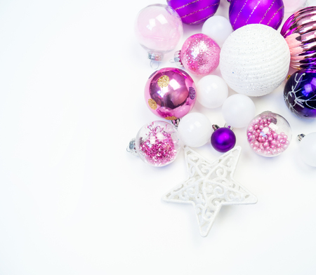 Gentle pink and purple baubles on a white background. Christmas mood. Festive decor. Sequins and glitter for a party.