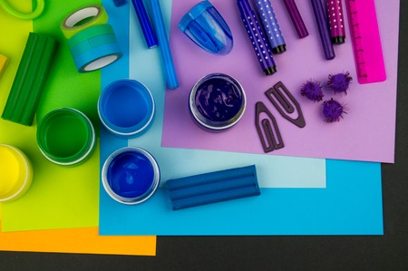 School accessories are laid out in the form of a rainbow. Black background.Happy back to school student. Art and crafts for kids. Child learning rainbow colors, alphabet letters and numbers. Banque d'images