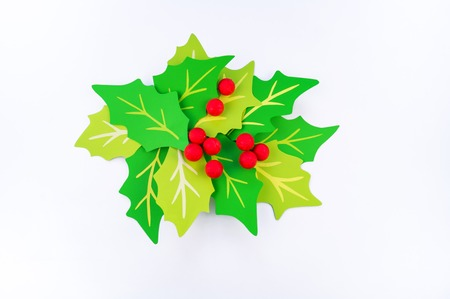 Flower holly made of paper crafts. Red berry from the ball. Christmas leaves. White background. Children's creativity.
