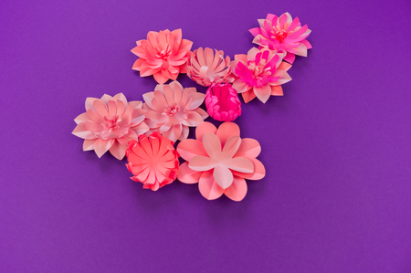 Flower made of coral color paper. The pink color of the curl and leaf. Purple background. Handmade florist. Favorite hobby of fused applique. Imagens