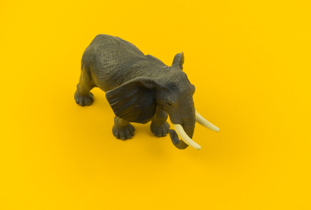 large plastic elephant toy on a yellow background. African animal for a child. Copy space.