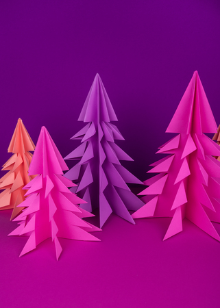 Christmas tree made of pink and purple craft paper. Handicraft. Violet background. Forest origami