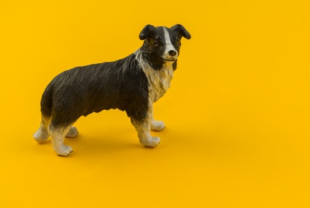 Toy dog from plastic on a yellow background  African animal for