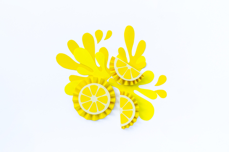Yellow lemon with splashes made of paper on a white background. Fruit smoothies vegetarian. Crafting creativity with children. Slice