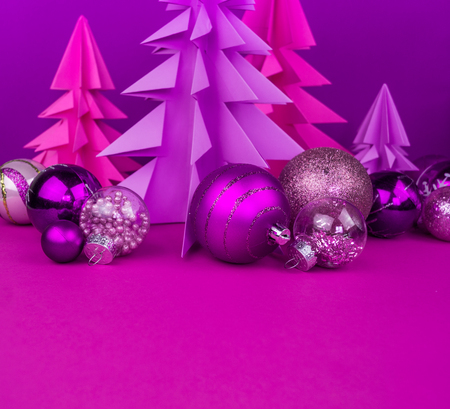 Christmas tree made of pink and purple craft paper. Handicraft. Violet background. Forest origami. Christmas ball baubles Stock Photo