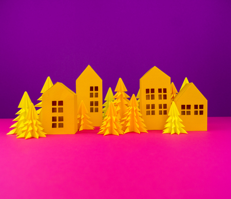 Christmas tree and house made of yellow craft paper. Handicraft . Violet and pink background. Forest Banco de Imagens