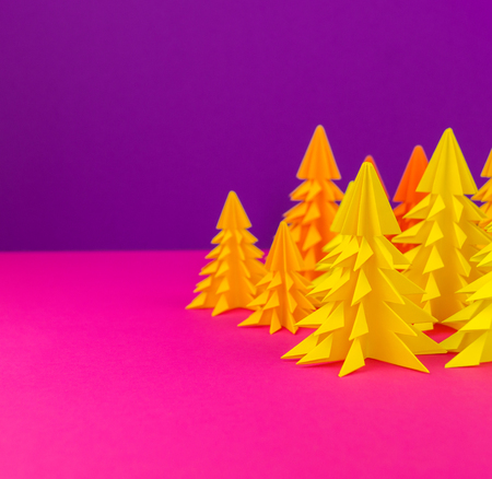 Christmas tree made of yellow craft paper. Handicraft. Violet and pink background. Forest