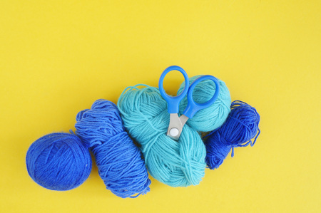 Blue ball of woollen thread. Yellow background. The view from the top.Material for a hobby. Knitting.