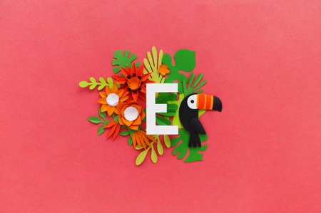 letter E of the alphabet cut out of white paper, surrounded by tropical flowers. Pink background. Lettering postcard. Handwork. Paper craft.