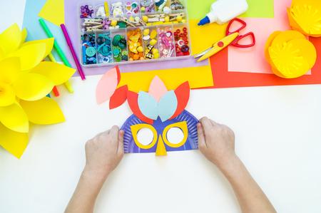 A child makes a bird mask out of paper. Master class crafts. Tropical Parrot. School, kindergarten. Children's hands cut, glue, make.