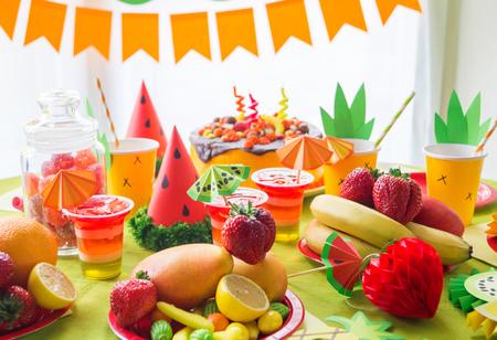 Decoración para una fiesta de cumpleaños infantil. Fiesta de frutas. Pastel y caramelo dulce. Vajilla desechable y frutas tropicales. Disfraz de sandía y piña.