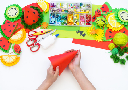 Paper cap for fruit party. Watermelon Birthday. Children's hands make crafts. Material for creativity and decoration. Master Class Stock Photo