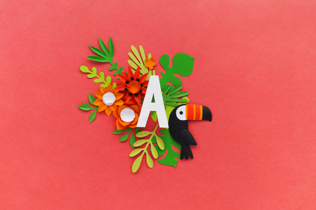 letter A of the alphabet cut out of white paper, surrounded by tropical flowers. Pink background. Lettering postcard. Handwork. Paper craft.