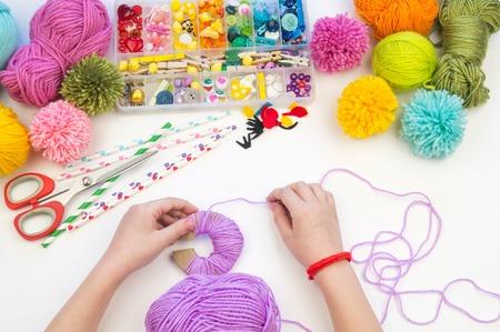 Das Kind beschäftigt sich mit einem Lieblingshobby. Das Kind macht einen Pompon aus einem Wollfadenmonster. Urlaub Spielzeug Geschenk. Kreativität mit Kindern. Schulkindergarten. Materialien zum Basteln.