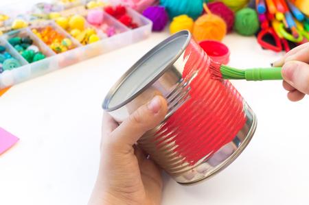 Kind macht aus einer Blechdose ein handgemachtes Einhorn. Regenbogenhaar Lieblings-Hobbyspielzeug. Material für Kreativität und Werkzeug. Weißer Hintergrund.