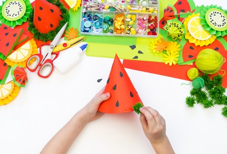 Paper cap for fruit party. Watermelon Birthday. Children's hands make crafts. Material for creativity and decoration. Master Class Zdjęcie Seryjne - 122560132