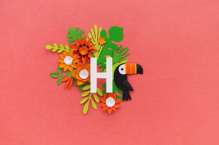 letter H of the alphabet cut out of white paper, surrounded by tropical flowers. Pink background. Lettering postcard. Handwork. Paper craft.