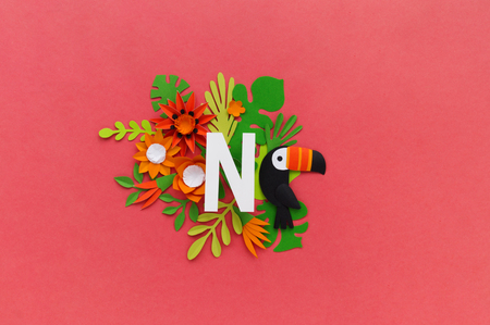 letter N of the alphabet cut out of white paper, surrounded by tropical flowers. Pink background. Lettering postcard. Handwork. Paper craft.