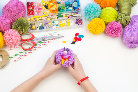 The child is engaged in a favorite hobby. The kid makes a pom-pom from a woolen thread monster. Holiday toy gift. Creativity with children. School kindergarten. Material for crafts.