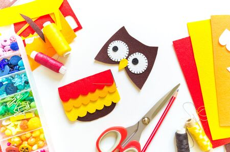 Owl made of felt. Workshop White background. Box with buttons and materials for creativity. Halloween Reklamní fotografie