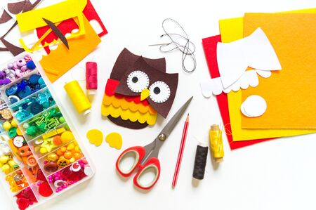 Owl made of felt. Workshop White background. Box with buttons and materials for creativity. Halloween Stock Photo