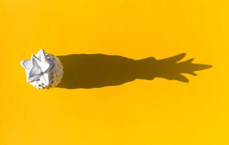 Piña de cerámica blanca sobre fondo amarillo. Sombra clara y brillante. Tendencia minimalista Foto de archivo