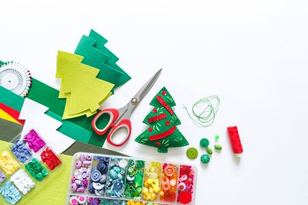 We sew a toy Christmas tree made of felt. New Year symbol. Material for decorating. Mastery is creativity.
