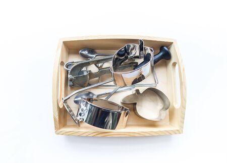 Material Montessori en una bandeja de madera sobre un fondo blanco. Juguetes de metal natural para el desarrollo sensorial de un niño. Toca las manos.