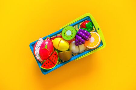 Children's toys vegetables fruits and products for the game of the store. Role play with a child. Flat lay The collection of games baby. yellow background