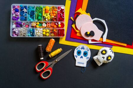 Dia de los Muertos Decorative paraphernalia decoration for the holiday Halloween. Black background. Monster felt soft toy.